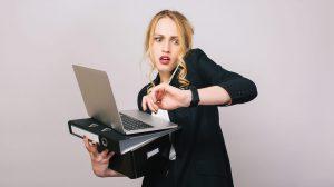 Nainen katsoo kelloa stressaantuneena